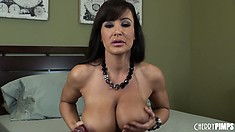 Lisa Ann gets down and dirty as she bangs her trimmed bush on the bed