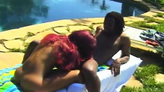 Luscious black babe with red hair takes on a dark stick under the sun