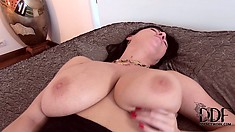 Lying on the bed, the stacked milf inserts every inch of that dildo in her peach