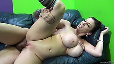 The busty milf lies by his side on the couch and has him pounding her pussy deep