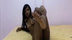 Pretty ebony Roxy uses her sexy feet to make a white nerd cum
