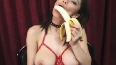 Japanese slut in bright red latex teases while eating a banana