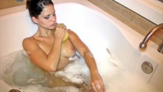 Busty Cali plays in the tub with her plastic duck and shaves her legs