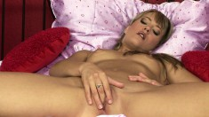 Adorable blonde lies on the bed and fucks her honey hole with a dildo