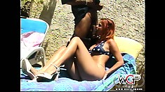 With the sun on her skin, a hot redhead babe enjoys her time with two black cocks